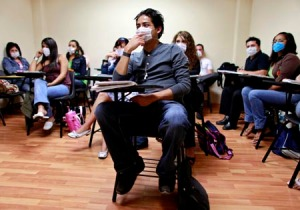 College students attend a class in labor law wearing masks to protect against the swine flu contagion, at Mexico City's University of London May 2009
