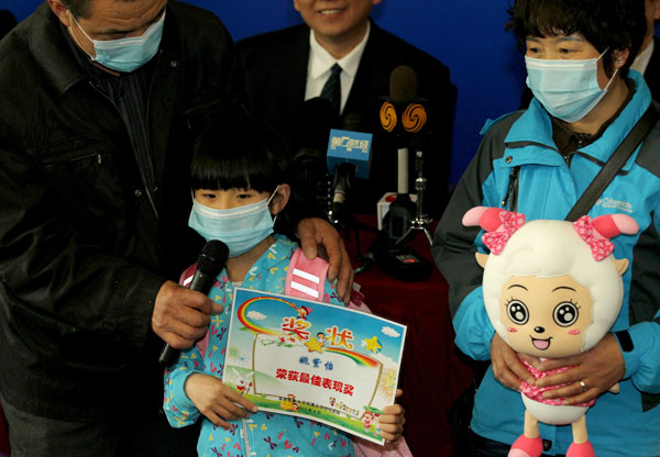The first H7N9 bird flu patient in Beijing, a girl surnamed Yao, accompanied by her parents, receives a certificate from Ditan Hospital for her brave composure during her hospitalization there. Yao was discharged on Wednesday. Wang Jing / China Daily